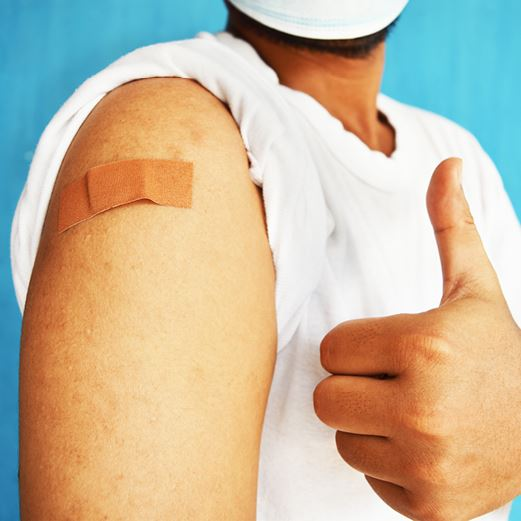 Vaccinated person gives thumbs up