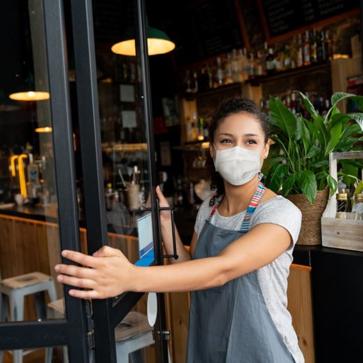 Woman in mask opens restaurant door